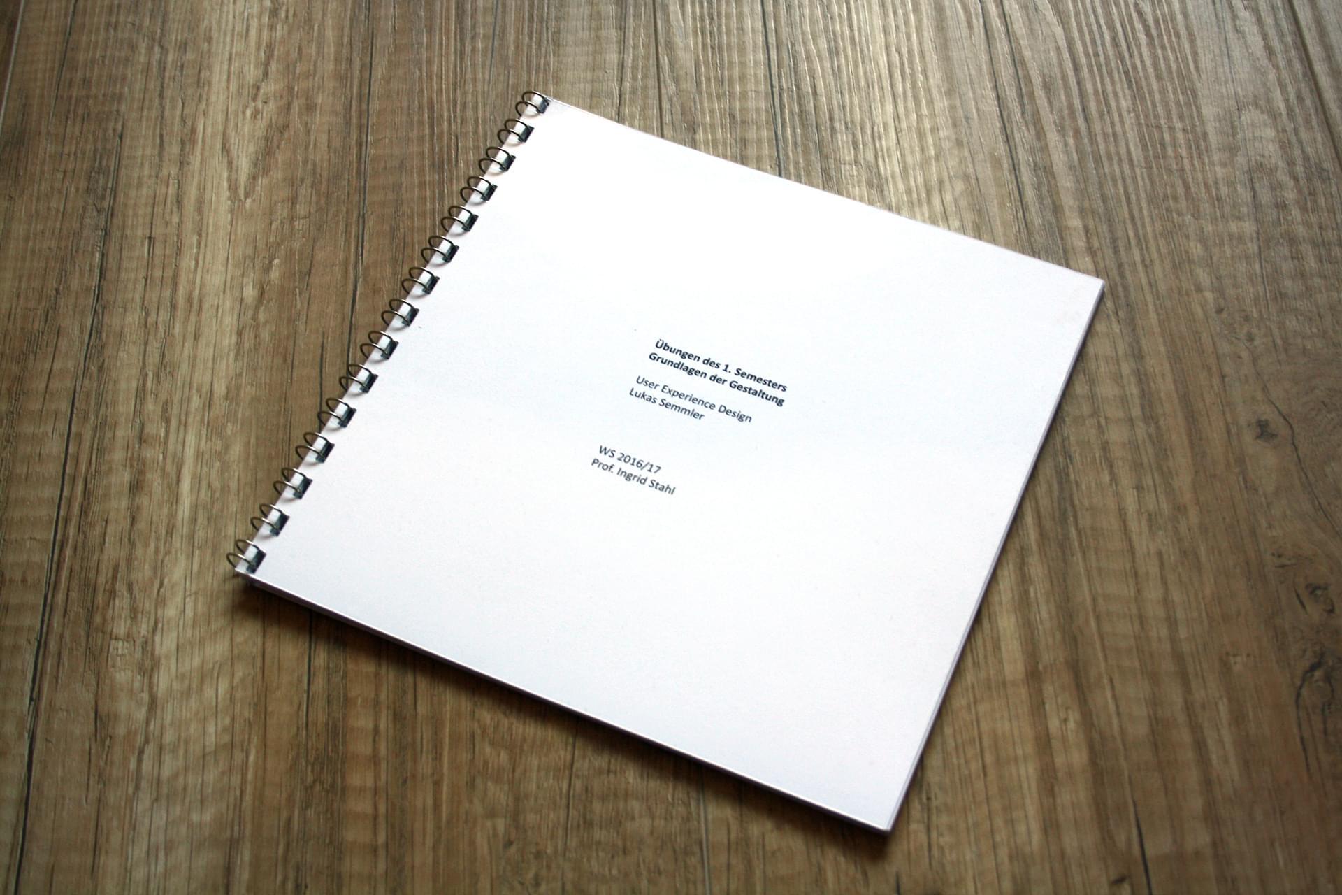 Das Booklet liegt mit dem Rücken auf einem holzähnlichem PVC-Boden.